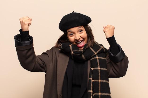 흥분되고 행복하고 놀란 승자처럼 보이는 히스패닉계 여성