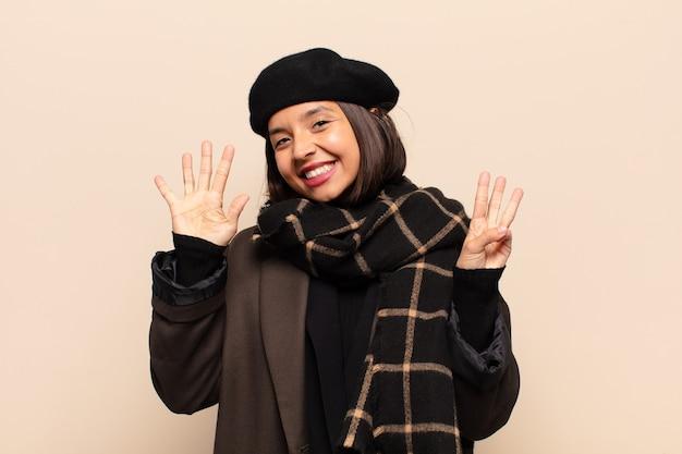 히스패닉계 여자가 웃고 친절하게보고, 앞으로 손으로 8 또는 8 번째를 보여주는, 카운트 다운