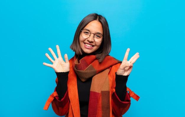 笑顔でフレンドリーに見えるヒスパニック系の女性、前に手を出して8番または8番を示し、カウントダウン