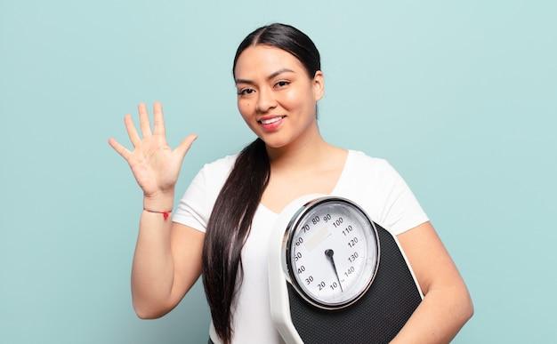 Латиноамериканская женщина улыбается и выглядит дружелюбно, показывает пятый или пятый номер рукой вперед и ведет обратный отсчет