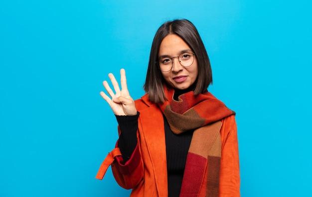 Латиноамериканская женщина улыбается и выглядит дружелюбно, показывает четвертый или четвертый номер рукой вперед и ведет обратный отсчет
