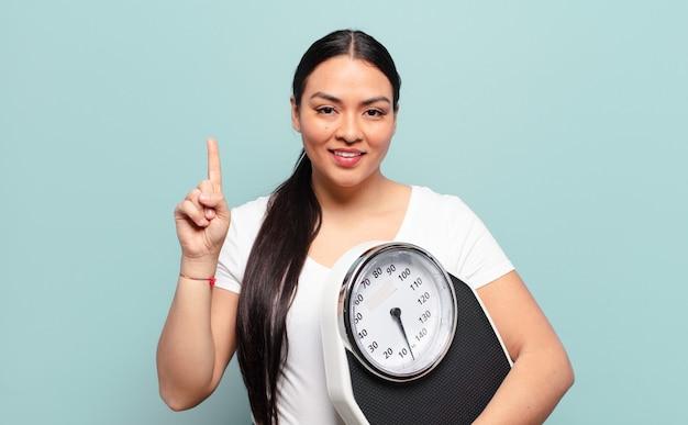 Латиноамериканская женщина улыбается и выглядит дружелюбно, показывает номер один или первый с рукой вперед, отсчитывает