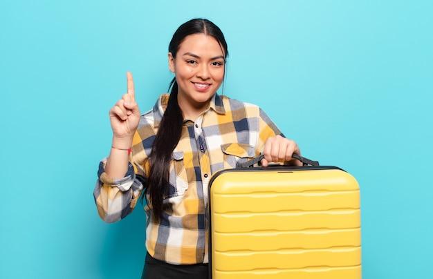 히스패닉계 여성이 미소하고 친절하게보고, 앞으로 손으로 번호 하나 또는 첫 번째 표시, 카운트 다운