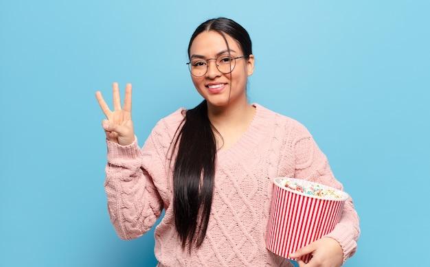Латиноамериканская женщина улыбается и выглядит дружелюбно, показывает номер три или треть рукой вперед, отсчитывает