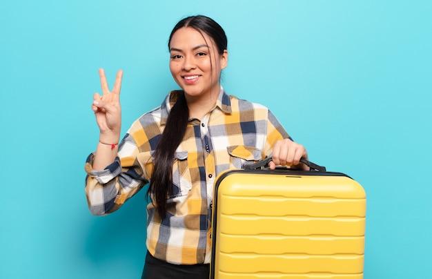 ヒスパニック系の女性が笑顔でフレンドリーに見え、手を前に向けて2番目または2番目を示し、カウントダウン