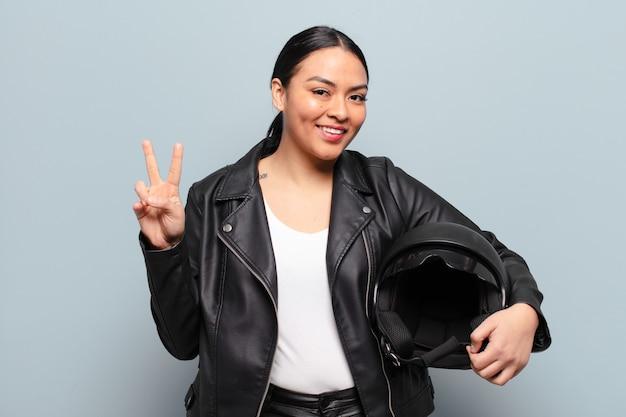笑顔で幸せそうに見えるヒスパニック系の女性、のんきで前向きで、片手で勝利や平和を身振りで示す