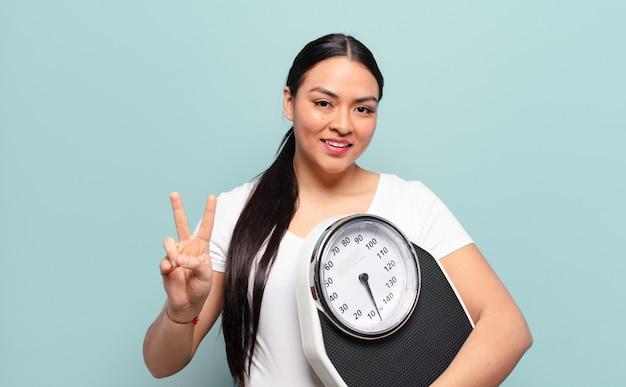 히스패닉계 여성이 웃고 행복하고 평온하고 긍정적 인 찾고 한 손으로 승리 또는 평화를 몸짓으로 나타냅니다.