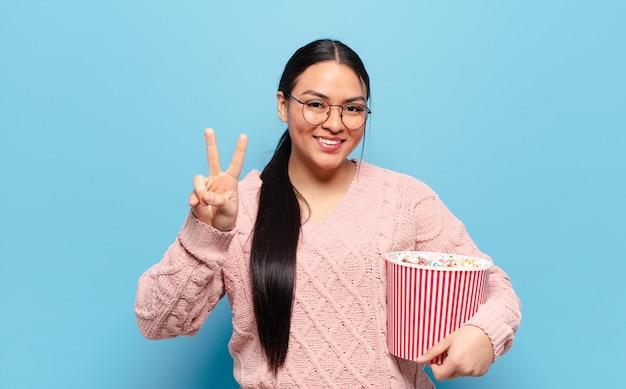 Латиноамериканская женщина улыбается и выглядит счастливой, беззаботной и позитивной, жестикулируя победу или мир одной рукой