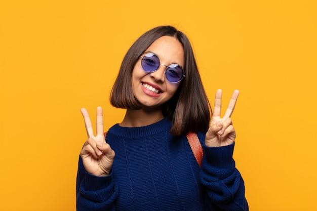 히스패닉계 여성이 웃고 행복하고 친절하며 만족스러워하며 양손으로 승리 또는 평화를 몸짓으로 표시합니다.