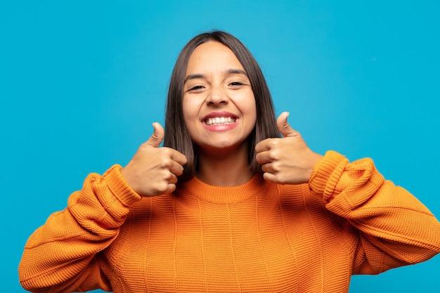 두 엄지 손가락으로 광범위하게 행복하고 긍정적이며 자신감이 넘치고 성공적인 미소를 짓는 히스패닉계 여성