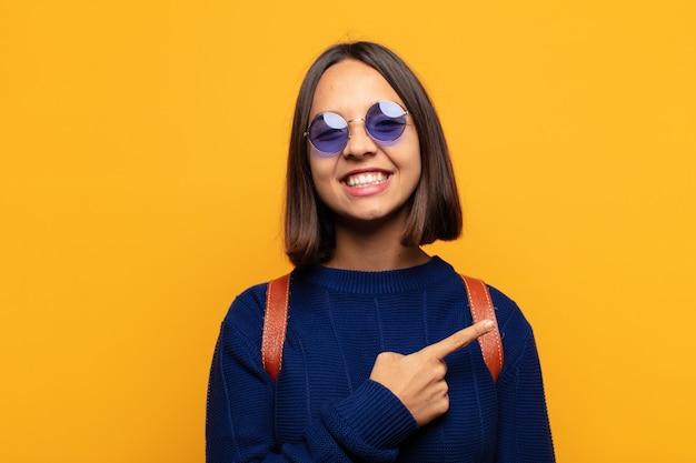 ヒスパニック系の女性は元気に笑って、幸せを感じて、横と上を指して、コピースペースにオブジェクトを表示します