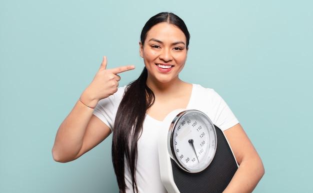 Латиноамериканская женщина уверенно улыбается, указывая на собственную широкую улыбку, позитивное, расслабленное, удовлетворенное отношение