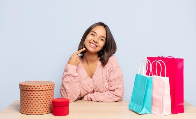 自信を持って微笑むヒスパニック系の女性が、自分の広い笑顔を指し示し、ポジティブでリラックスしている
