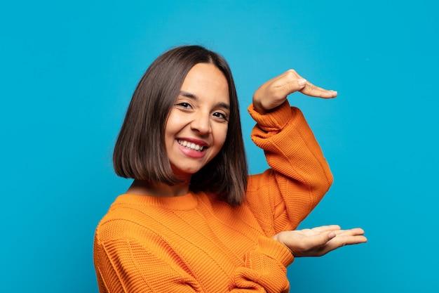 히스패닉계 여자 웃고, 행복하고, 긍정적이고 만족스럽고, 들고 또는 복사 공간에 개체 또는 개념을 보여주는