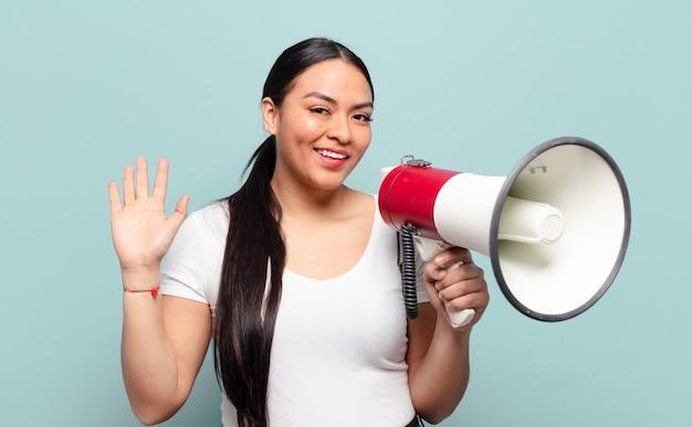 Латиноамериканская женщина счастливо и весело улыбается, машет рукой, приветствует и приветствует вас или прощается