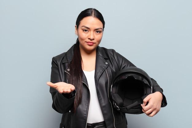 Латиноамериканская женщина счастливо улыбается, дружелюбно, уверенно, позитивно смотрит, предлагая и показывая объект или концепцию