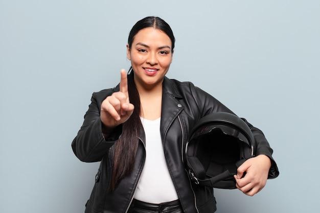 ヒスパニック系の女性が誇らしげに自信を持って笑顔でナンバーワンのポーズを勝ち誇って、リーダーのように感じています