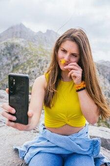 スマートフォンで自分撮りをして山の花の匂いを嗅ぐヒスパニック系女性