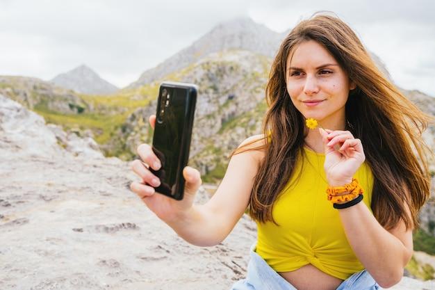 山でスマートフォンで自分撮りをしているヒスパニック系女性