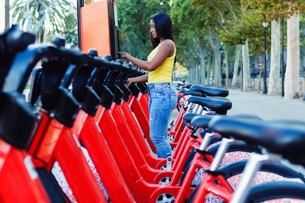 Hispanic woman taking bicycle in the city - young latin female unlocking bike share on street