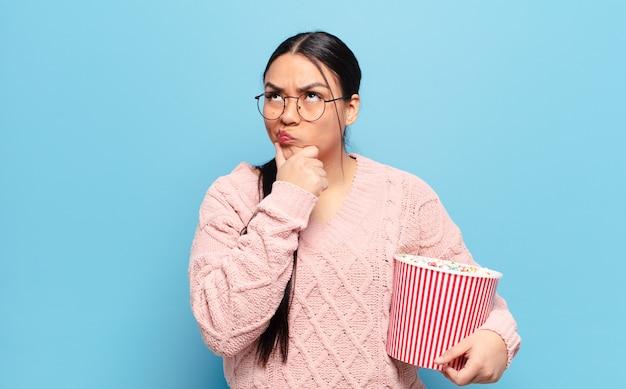 Латиноамериканская женщина думает, чувствует себя сомневающейся и сбитой с толку, с разными вариантами, задаваясь вопросом, какое решение принять