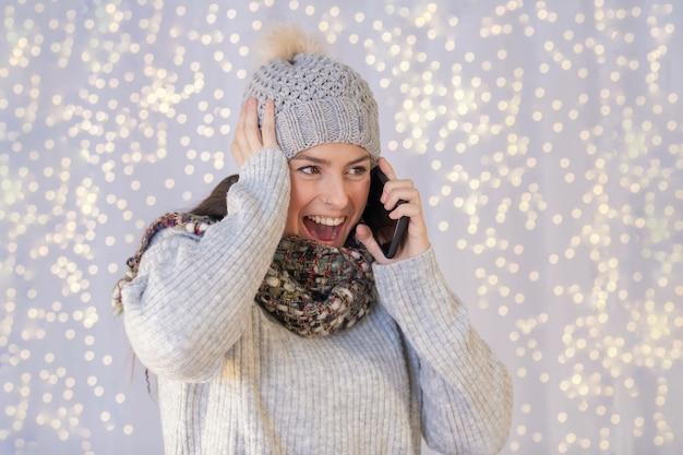 暖かいセーターと帽子をかぶって、電話で話しているヒスパニック系の女性は非常に興奮しています