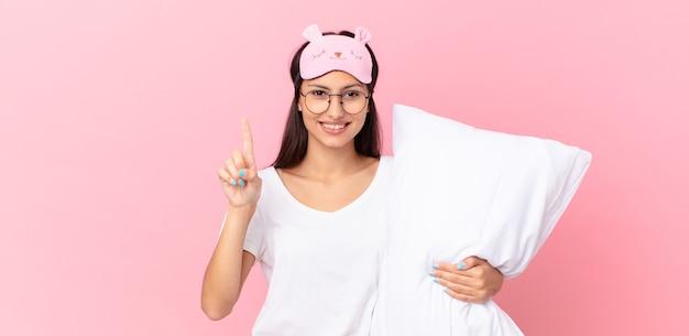 웃 고 친절 하 게 찾고, 번호 하나를 표시 하 고 베개를 들고 잠 옷을 입고 히스패닉계 여자