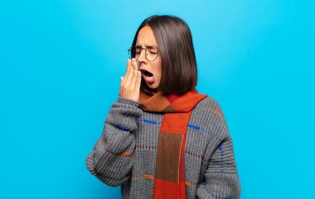 ヒスパニック系の女性が朝早くに怠惰にあくびをし、目を覚まし、眠く見え、疲れて退屈している