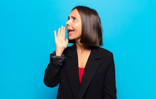 Hispanic woman yelling loudly and angrily to copy space on the side, with hand next to mouth