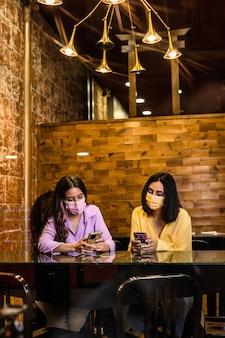 Молодые латиноамериканские подруги используют смартфоны в ресторане, чтобы заказывать ужин и болтать ношение маски для лица образ жизни независимых женщин вместе желтый и лавандовый цвет 2021