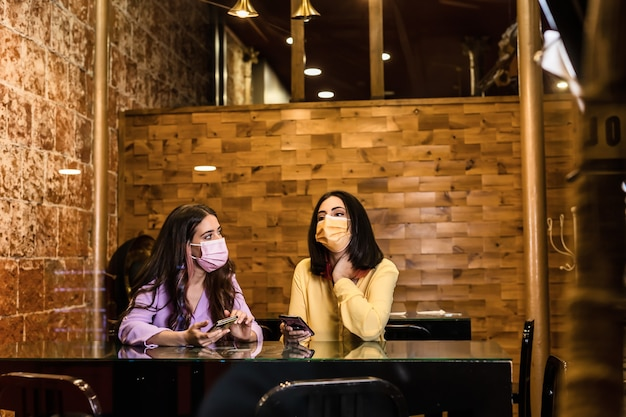 Hispanic young female friends using smartphone technology in restaurant to order dinner and chatting wearing face mask lifestyle from independent women together yellow and lavender color 2021