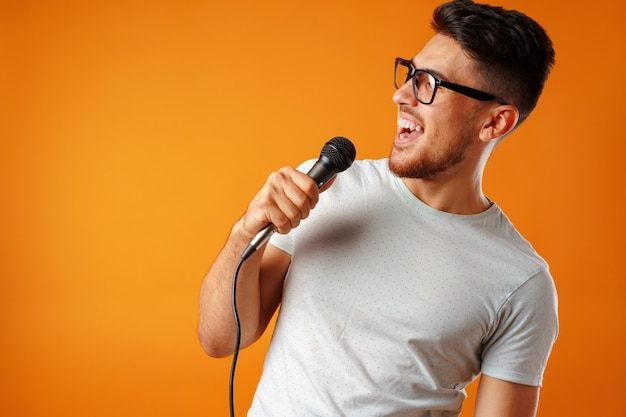 ヒスパニック系の若いハンサムな男がマイクclsoeで喜びを持って歌う
