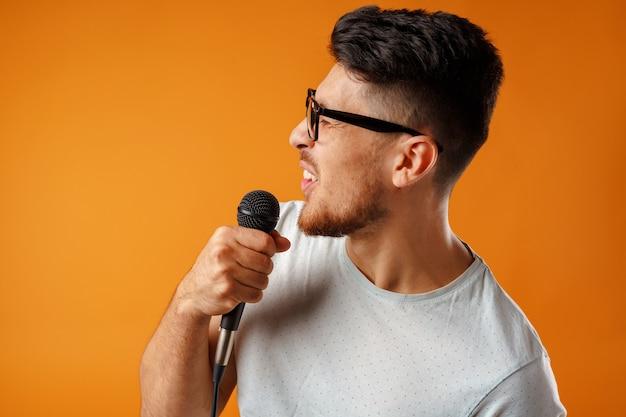マイクで喜びと歌うヒスパニック系の若いハンサムな男