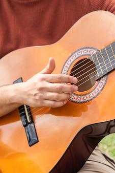Испаноязычное молодой человек играет на гитаре, сидя в парке
