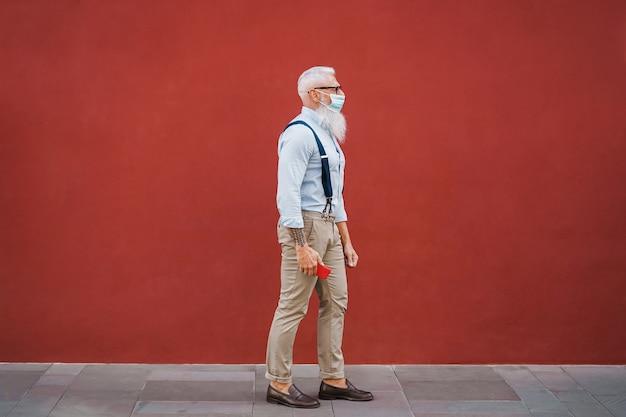 安全マスクを使用して街を歩いているヒスプターの年配の男性-顔に焦点を当てる