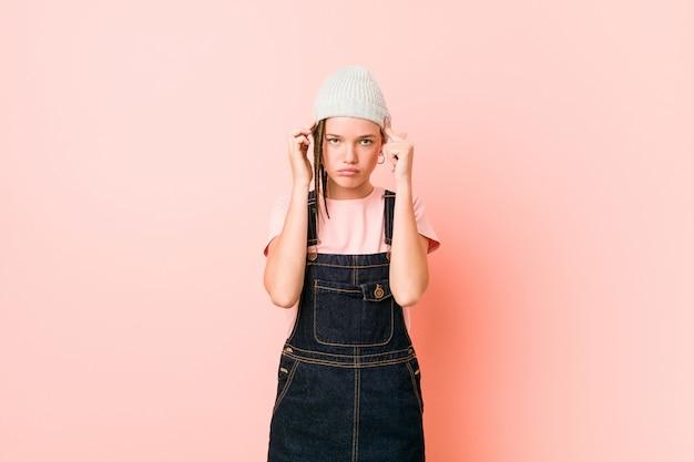 Hispterの10代の女性は、人差し指を頭に向けたまま、タスクに集中しました。