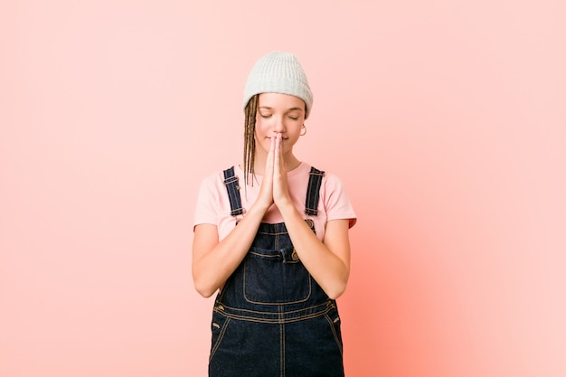 Hispter teenager woman holding hands in pray near mouth, feels confident.