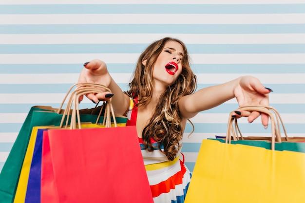 カラフルな紙袋を持っている歴史的な女性の買い物中毒者。ショッピング後の縞模様の壁にポーズをとるブルネットの長い髪の女性の屋内の肖像画。