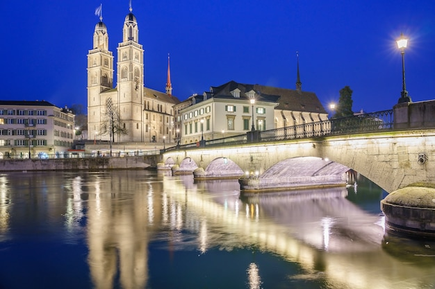 Historic city of zurich with famous grossmunster church and munsterbucke on twilight time