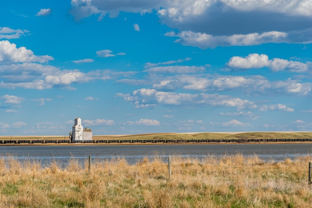 The historic grain elevator with railroad cars and water in sanctuary, saskatchewan