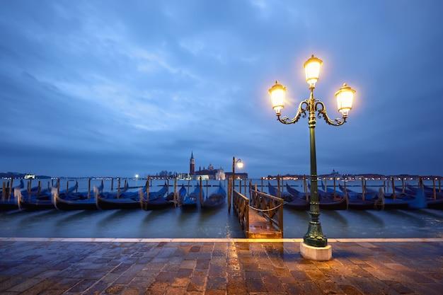 베니스, 이탈리아에서 밤에 goldolas와 역사적인 램프 게시물