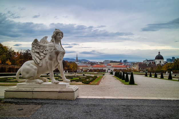Historical landscape with marble sculpture of woman sphinx on a parapet of schloss belvedere palace in vienna, austria on a background of grey cloudy sky on autumn day.