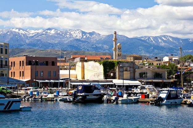 Historical venetian harbor in chania, crete, greece. sea and mountains, sunny day