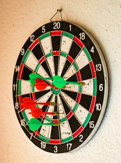 Hit group of target in dart game on wall.