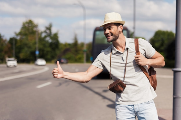 Hitch-hike travel happy man catches car in city.