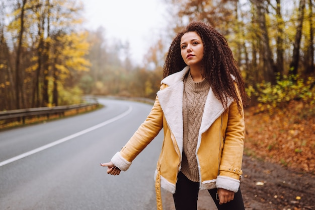 Hitchhiker afro haired woman waiting for a car on the road in the forest at autumn. woman wearing yellow jacket.