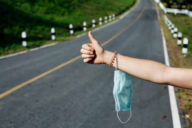 Autostoppista che tiene mascherina medica su un'autostrada