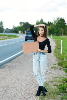 Hitchhiker on the road is holding a blank cardboard sign