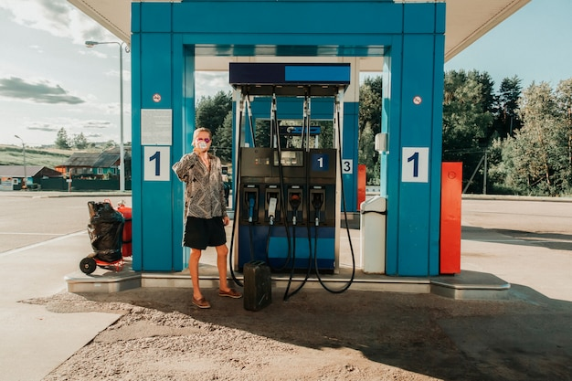 Hitchhiker in sunglasses drinking water on the rural blue filling station of russia on a sunny day.
