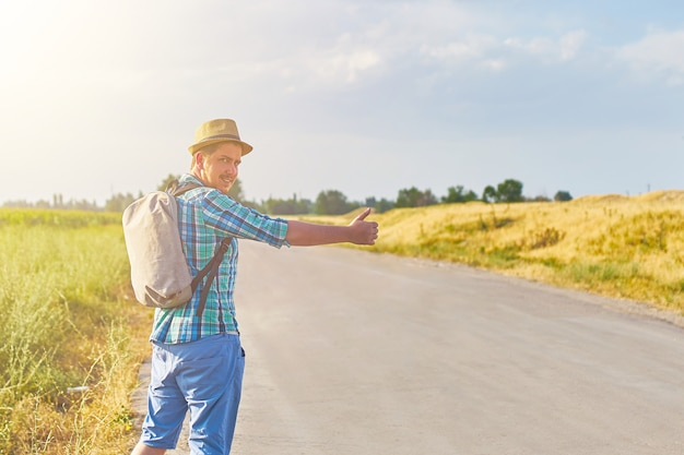 Hitchhiker with backpack in summer hat, light shirt, shorts on the road in tropical country